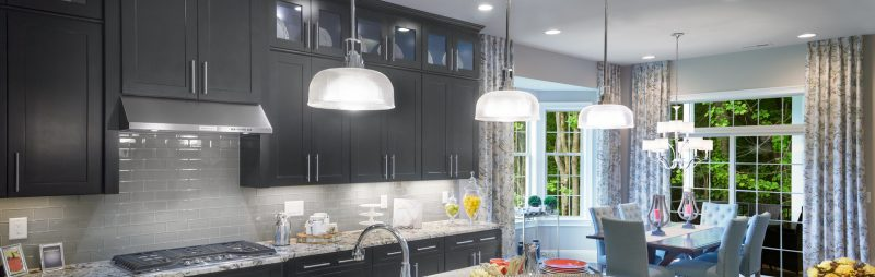 A row of hanging lamps in an arid and modern kitchen.
